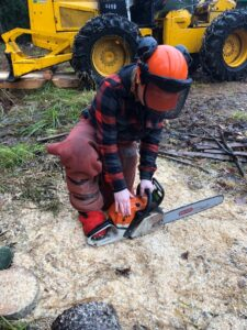 Woman starting a chainsaw